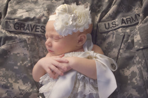 Kansas City Newborn Photographer | Newborn girl in ivory headband on military uniform