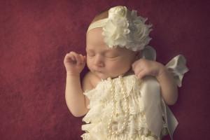 Kansas City Newborn Photographer | Baby girl in ivory romper on magenta background