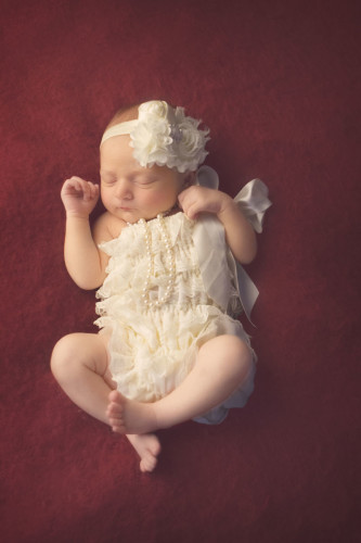 Kansas City Newborn Photographer   Baby girl in ivory romper on magenta background