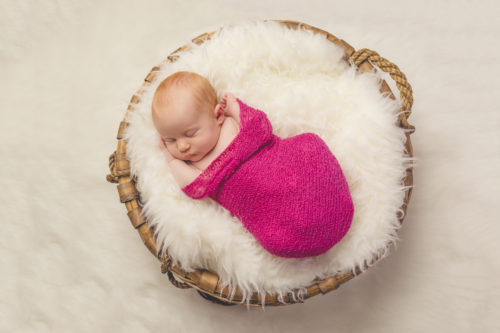 Kansas City Newborn Photographer | Baby girl in fur-stuffed basket
