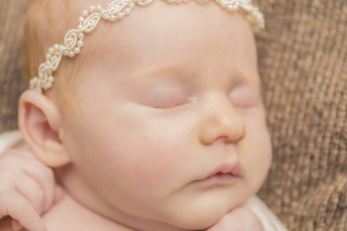 Kansas City Newborn Photographer | Baby girl on brown background with ivory bow