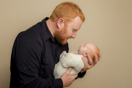 Kansas City Newborn Photographer | Red-head dad holding red-head baby girl