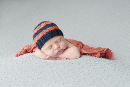 Kansas City Newborn Photographer | Newborn boy on blue backdrop with blue and orange hat