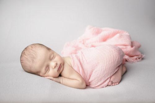 kansas city newborn photographers | image of newborn baby girl wrapped in pink swaddle