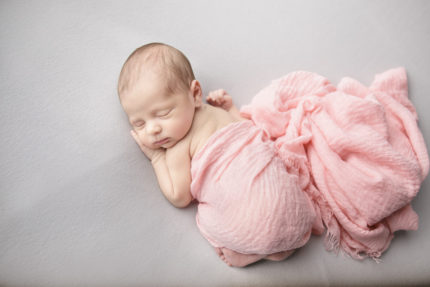 kansas city newborn photographers | image of newborn baby girl wrapped in pink swaddle