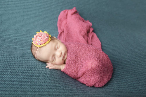 kansas city newborn photographers   picture of newborn wrapped in pink with yellow and pink bow
