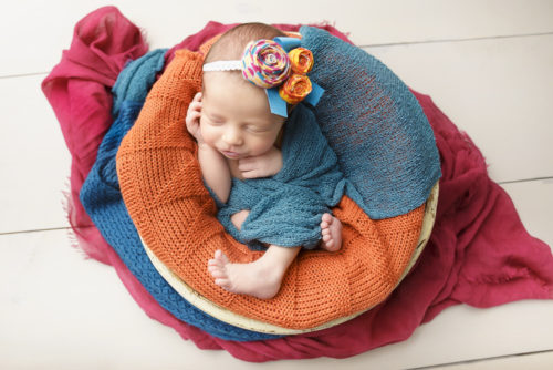 kansas city newborn photographers | picture of newborn baby girl in bucket surrounded by bright colors