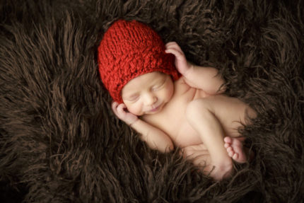 kansas city newborn photographer | pictures of newborn on brown fur with red bonnet