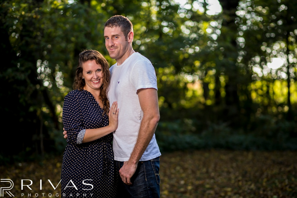 Schwinn Produce Farm Sunflower Engagement Pictures | A picture of an engaged couple embracing surrounded by greenery.