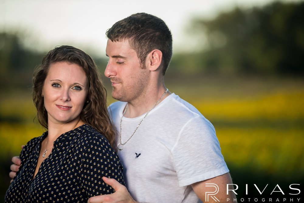 Schwinn Produce Farm Sunflower Engagement Pictures | An close-up photo of an engaged couple standing in front of fields of sunflowers.
