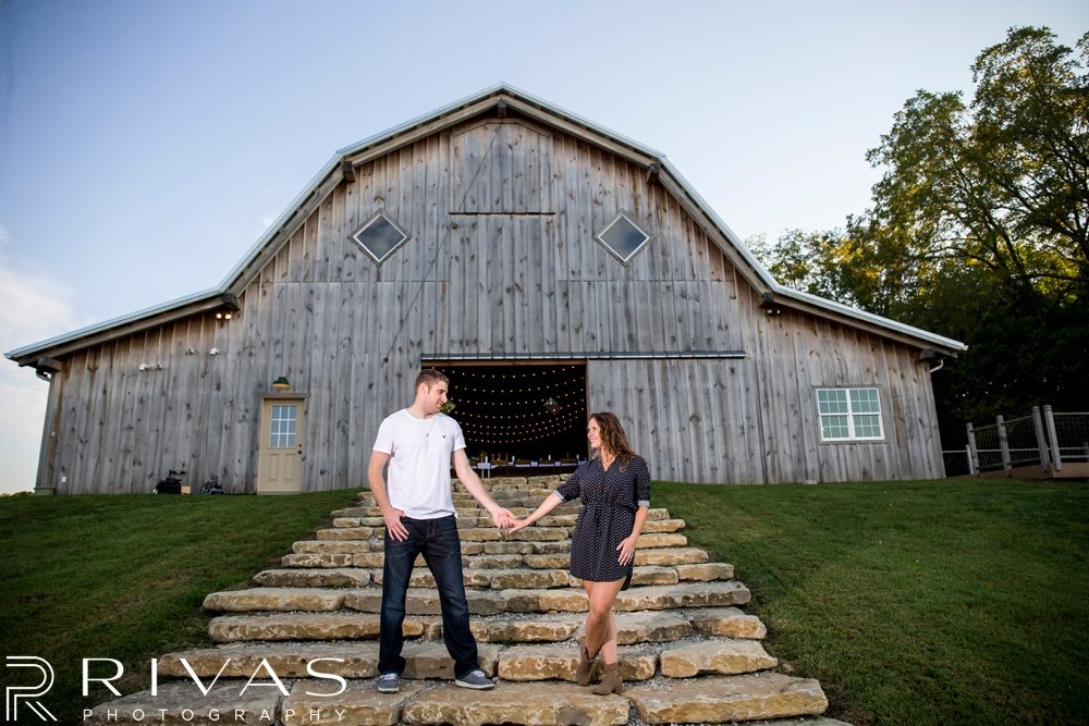 Schwinn Produce Farm Sunflower Engagement Pictures | A picture of an engaged couple holding hands standing in front of an old barn.