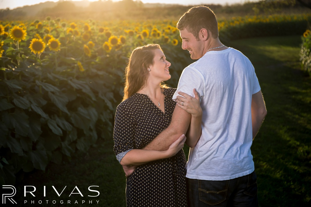 Schwinn Produce Farm Sunflower Engagement Pictures | A close-up picture of an engaged couple embracing surrounded by fields of sunflowers.