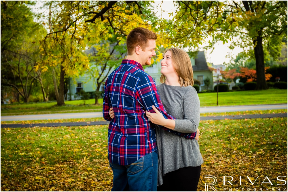 Colorful Fall Engagement Session | A close-up photo of an engaged couple embracing under colorful trees at Loose Park.