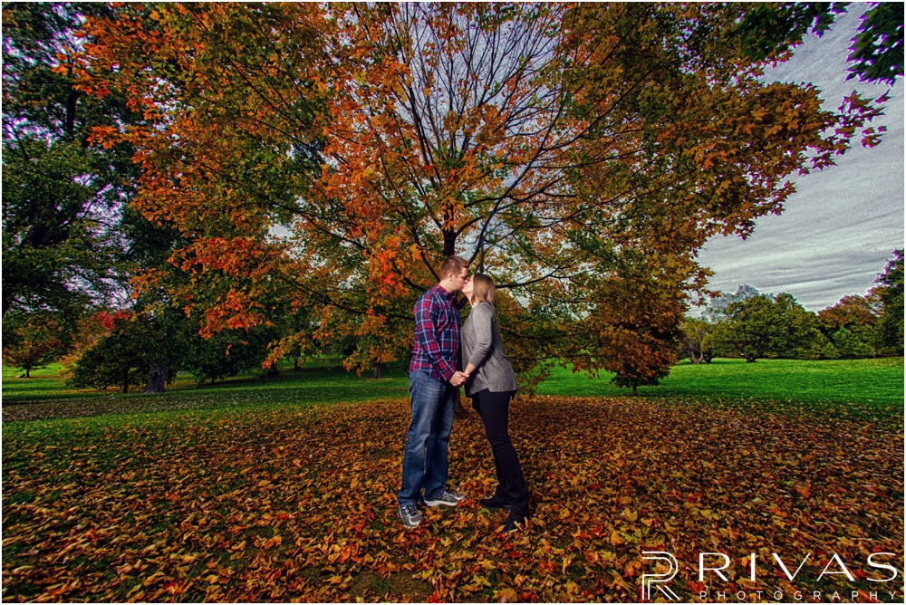 Colorful Fall Engagement Session | An image of an engaged couple sharing a kiss underneath a tree covered in orange leaves at Loose Park.