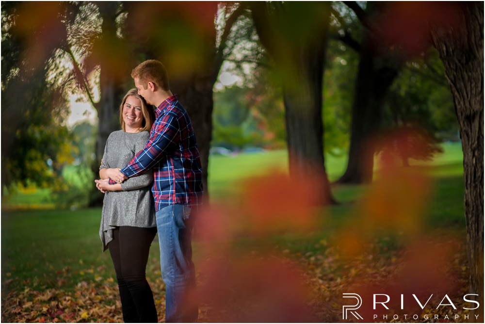 Colorful Fall Engagement Session | An image of an engaged couple embracing underneath a tree covered in orange leaves at Loose Park.