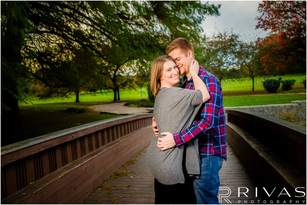 Colorful Fall Engagement Session |  A photo of an engaged couple embracing on a wooden bridge at Loose Park.