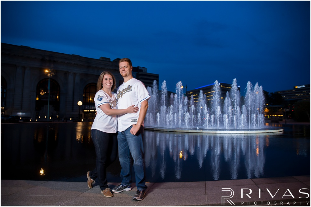 Colorful Fall Engagement Session |  An image of an engaged couple embracing in front of the fountain outside Kansas City's Union Station at dusk.
