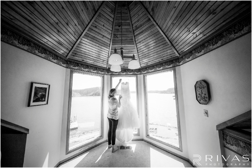 Lake of the Ozarks Elopement | A photo of a bride reaching to pull her wedding gown off the hanger.