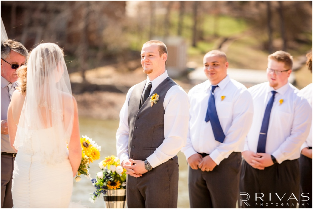 Lake of the Ozarks Elopement | A candid photo of a groom looking at his bride during their lakeside wedding ceremony.