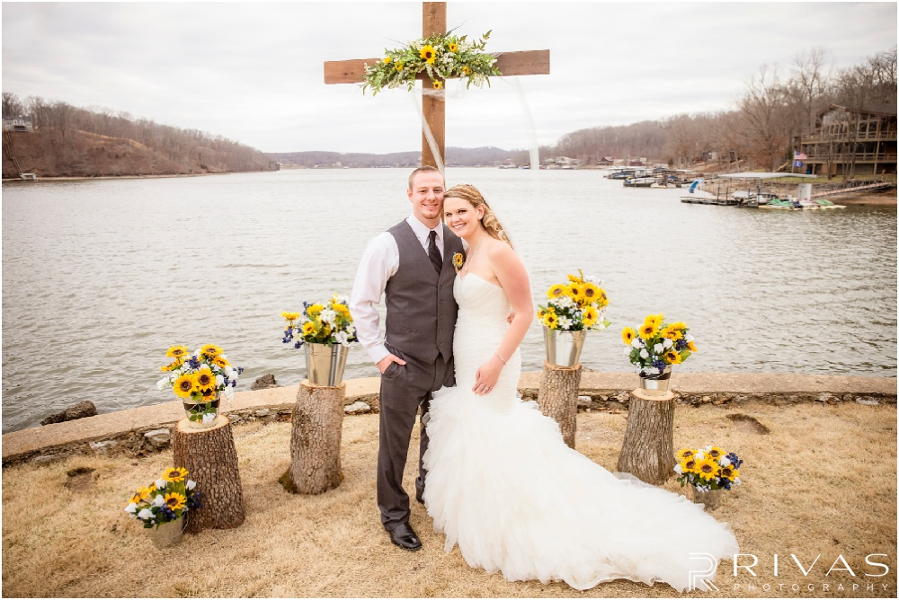 Lake of the Ozarks Elopement | A picture of a bride and groom underneath the cross the groom built and installed that served as their alter during their lakeside wedding ceremony.