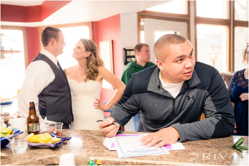 Lake of the Ozarks Elopement | A candid picture of a best man signing the marriage license at a lake-house reception.