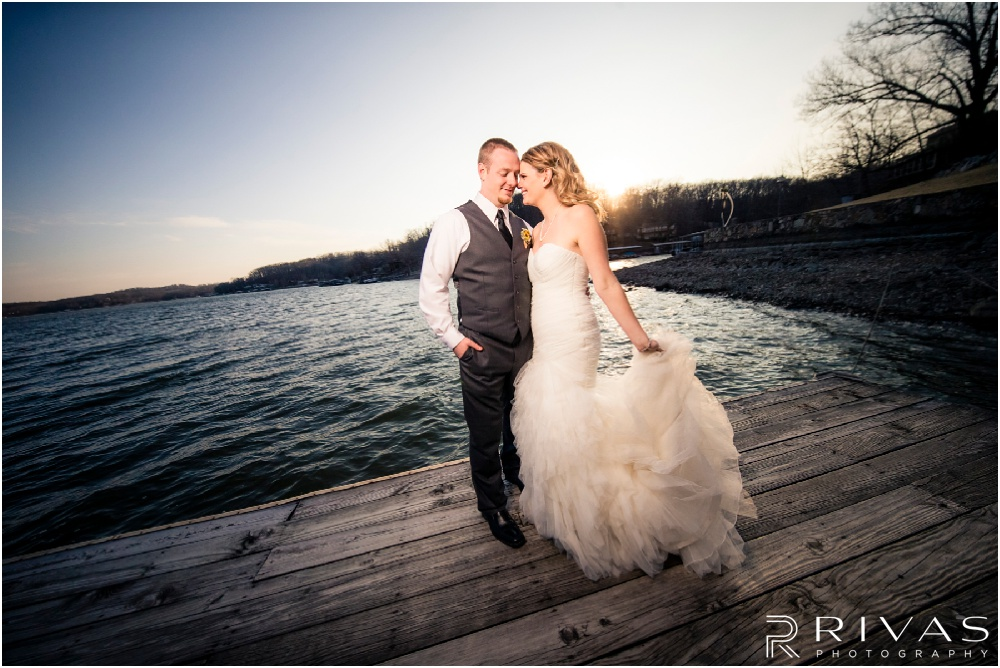 Lake of the Ozarks Elopement | A photo of a bride and groom standing on a dock at sunset.