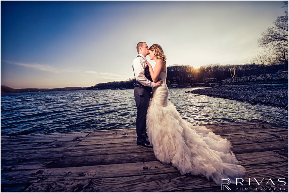 Lake of the Ozarks Elopement | A picture of a bride and groom standing on a dock at sunset.