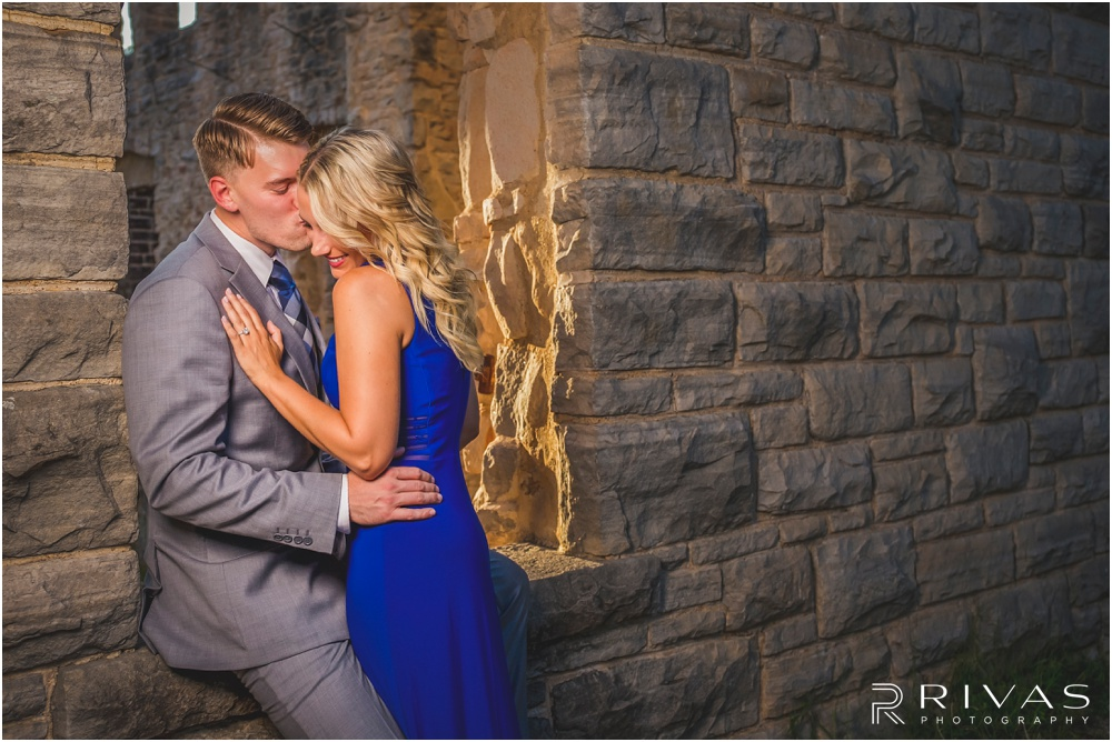 romantic castle ruins engagement pictures | An image of an engaged couple dressed up leaning against a stone wall at sunset.