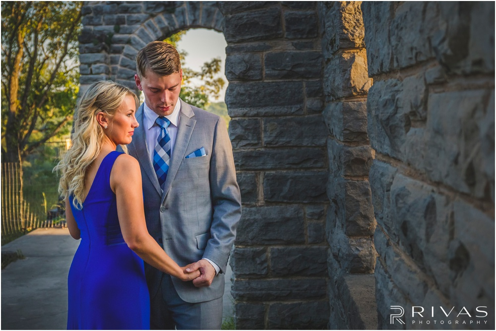 romantic castle ruins engagement pictures | A photo of an engaged couple holding hands near a stone wall.