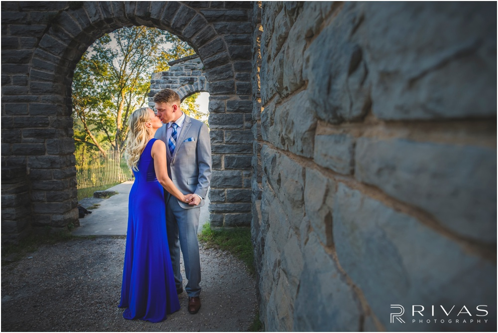 romantic castle ruins engagement pictures | A photo of an engaged couple holding hands and kissing near a stone wall.