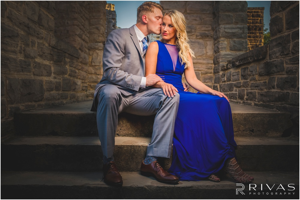 romantic castle ruins engagement pictures | A picture of an engaged couple holding hands while sitting at the top of a flight of stairs.