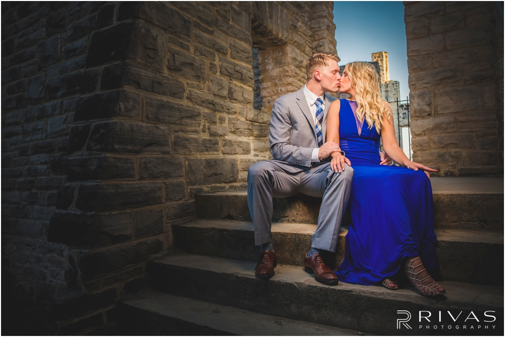 romantic castle ruins engagement pictures | A picture of an engaged couple kissing while sitting at the top of a flight of stairs.