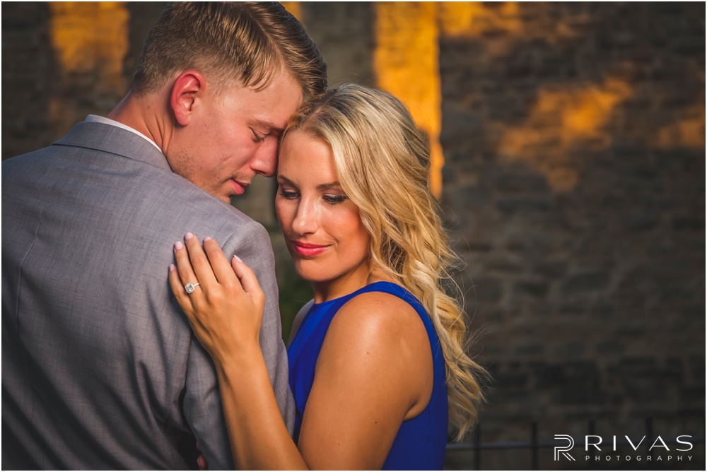 romantic castle ruins engagement pictures | An image of a bride peeking over a groom's shoulder.