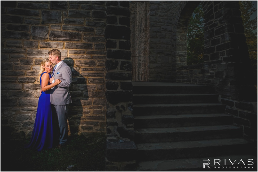 romantic castle ruins engagement pictures | A dramatic picture of an engaged couple embracing near a stone wall.