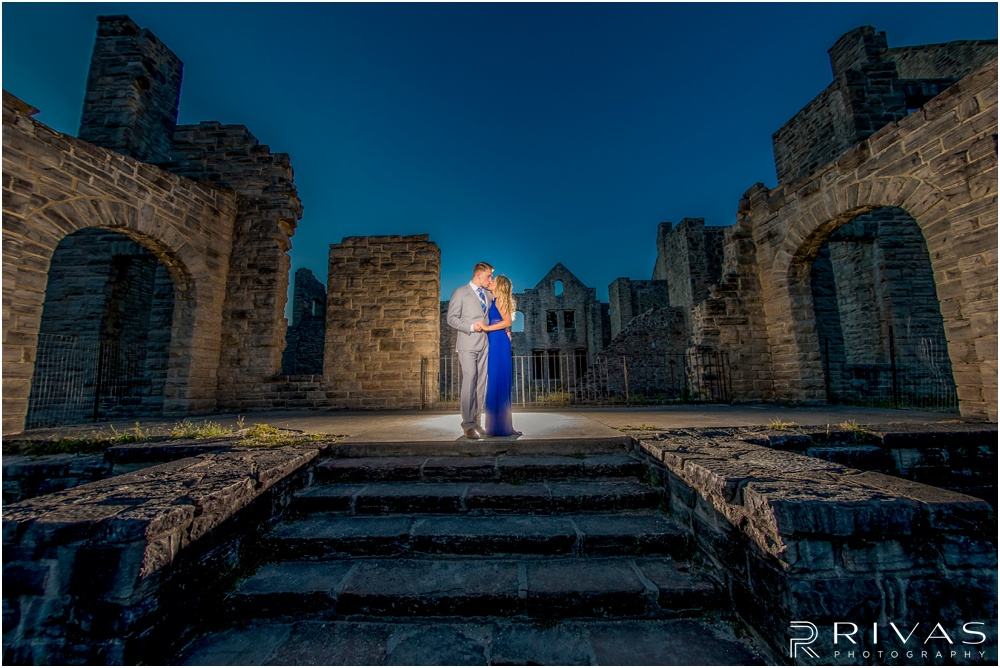 romantic castle ruins engagement pictures | A picture of an engaged couple embracing on stairs leading to castle ruins.