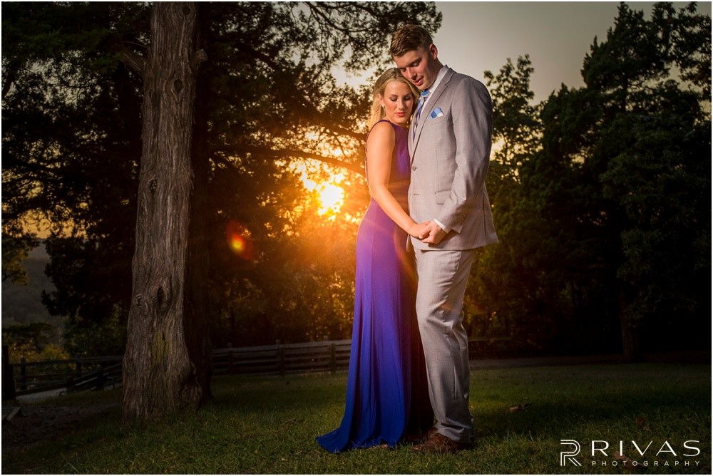romantic castle ruins engagement pictures | A photo of an engaged couple embracing on the lawn of castle ruins at sunset.
