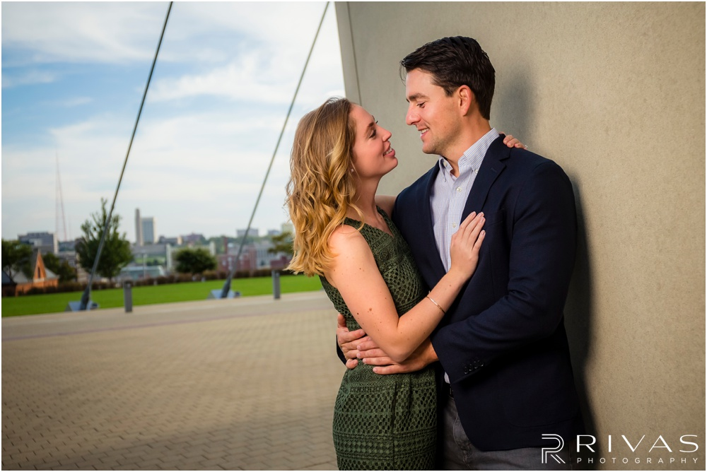 Elegant Kauffman Center Engagement Pictures | A picture of a dressed up couple hugging near the Kauffman Center for the Performing Arts.