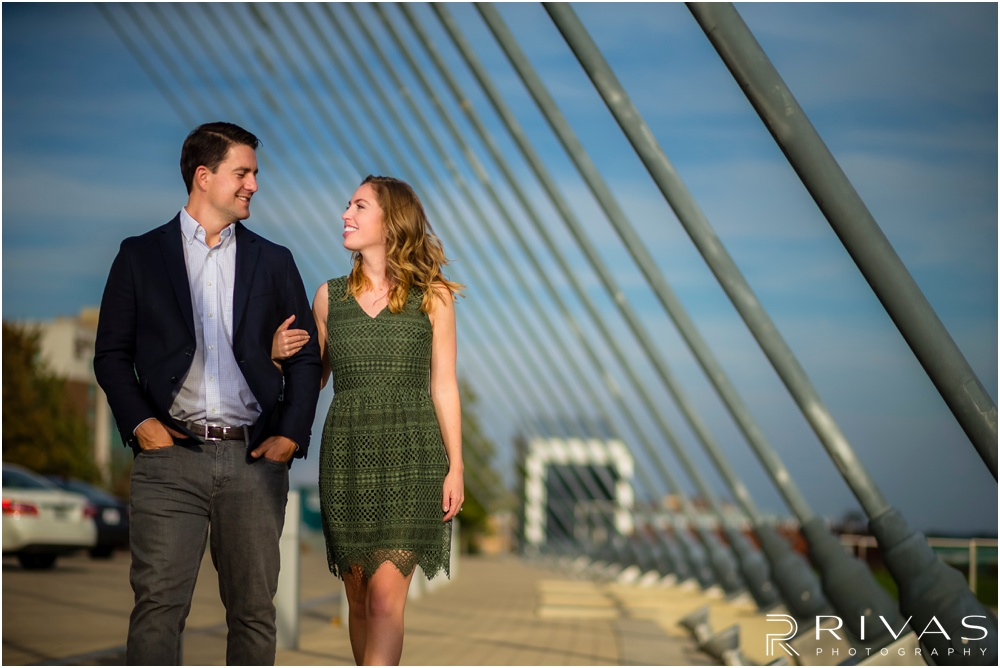 Elegant Kauffman Center Engagement Pictures | A candid picture of a dressed up engaged couple walking on the south side of the Kauffman Center for the Performing Arts.