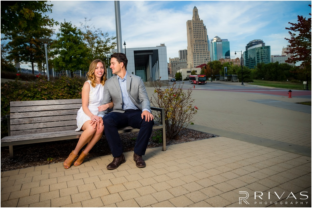 Elegant Kauffman Center Engagement Pictures | A candid picture of a dressed up engaged couple sitting together on the east side of the Kauffman Center for the Performing Arts.