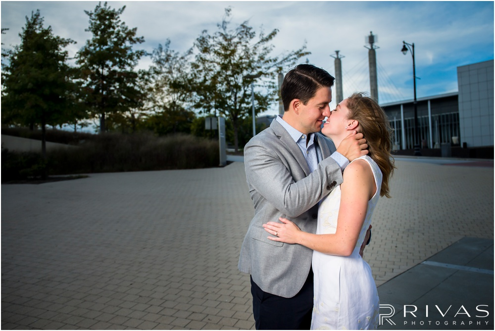 Elegant Kauffman Center Engagement Pictures | A close-up candid picture of a dressed up engaged couple kissing on the east side of the Kauffman Center for the Performing Arts.
