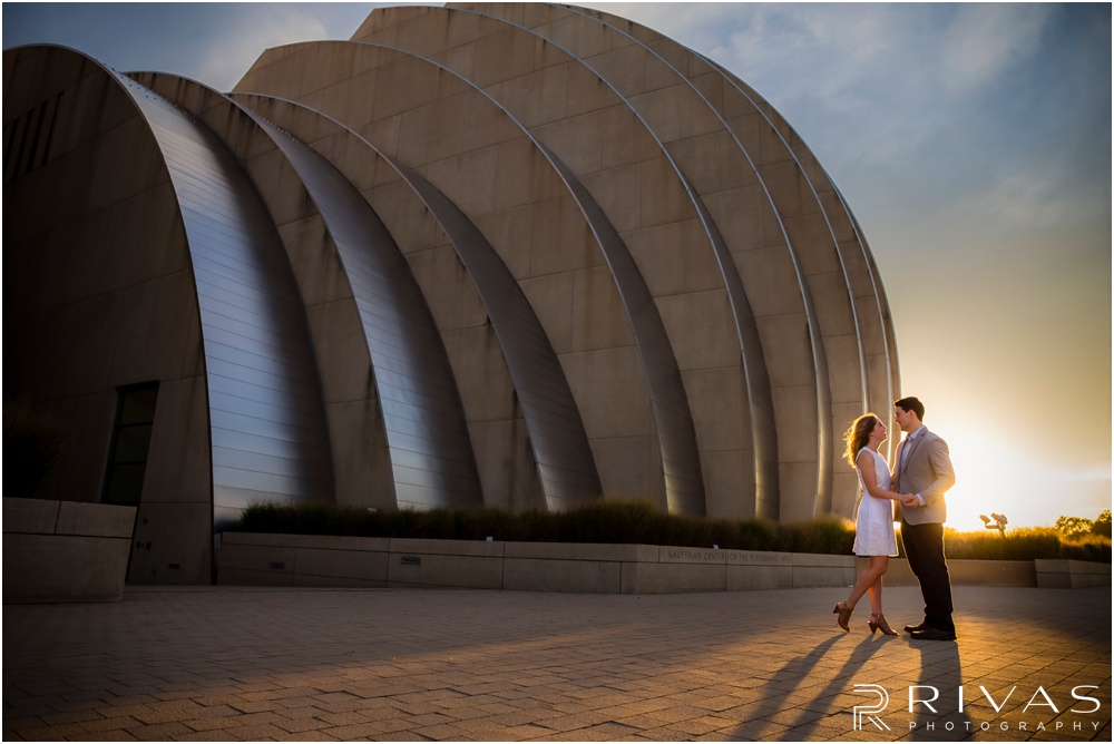 Elegant Kauffman Center Engagement Pictures | A picture of a dressed up engaged couple holding hands on the north side of the Kauffman Center for the Performing Arts.