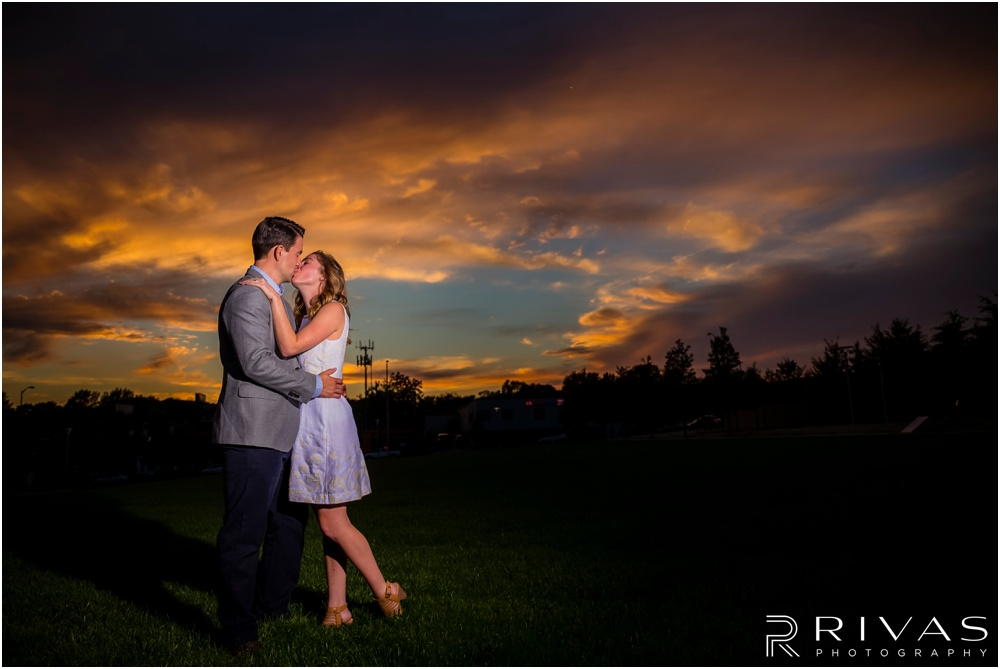 Elegant Kauffman Center Engagement Pictures | A photo of a dressed up engaged couple kissing in front of sunset on the south lawn of the Kauffman Center for the Performing Arts.
