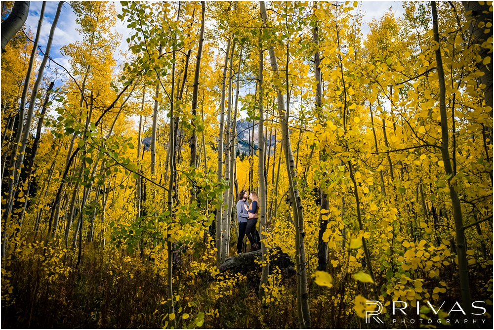 Fall Aspen Engagement Session | A picture of a couple in fall sweatshirts standing on a boulder in a grove of yellow aspens outside Aspen, Colorado.