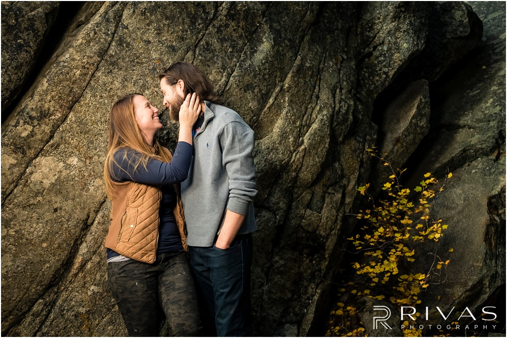 Fall Aspen Engagement Session | A photo of a couple in fall sweatshirts standing in front of a large boulder at a roadside park outside Aspen, Colorado.