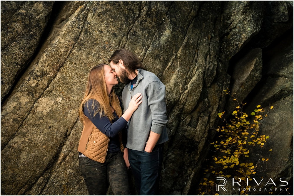 Fall Aspen Engagement Session | A photo of a couple in fall sweatshirts kissing in front of a large boulder at a roadside park outside Aspen, Colorado.