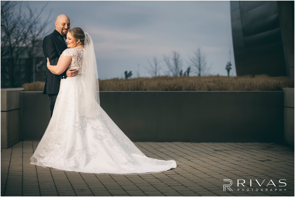 Spring Wedding Sneak Peek | A dramatic photo of a bride and groom hugging in front of The Kauffman Center for the Performing Arts in Kansas City.