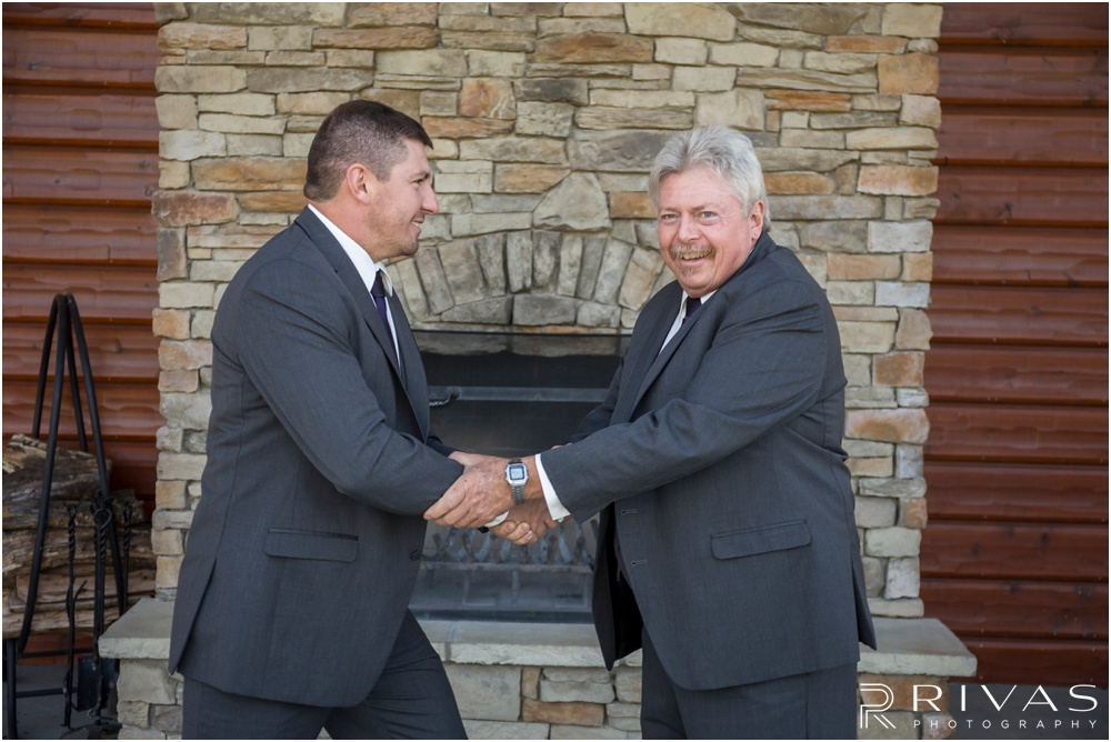 elegant fall wedding buffalo lodge | A picture of a groom shaking his dad's hand on the Buffalo Lodge patio.