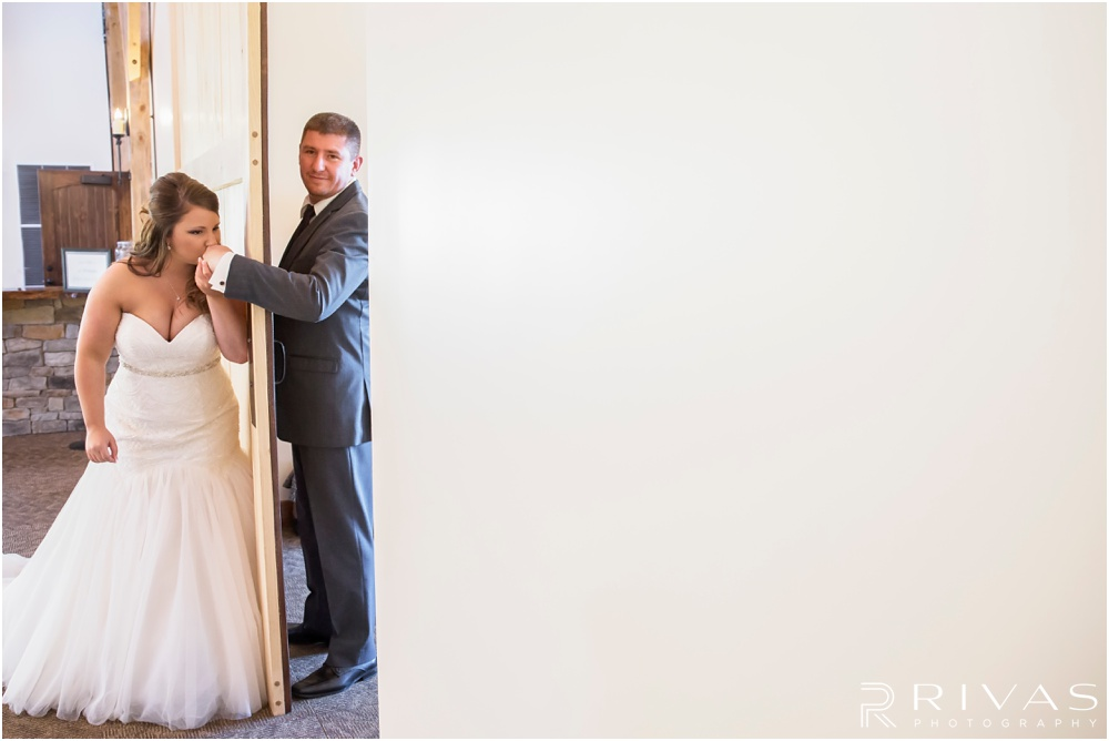 elegant fall wedding buffalo lodge | A candid photo of a bride and groom talking to each other around a sliding door at The Buffalo Lodge.