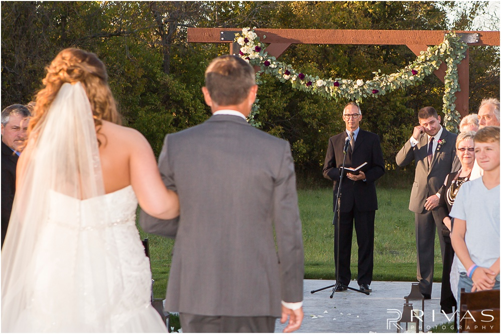 elegant fall wedding buffalo lodge | A picture of a groom wiping tears from his eyes as he sees his bride walk down the aisle at The Buffalo Lodge.