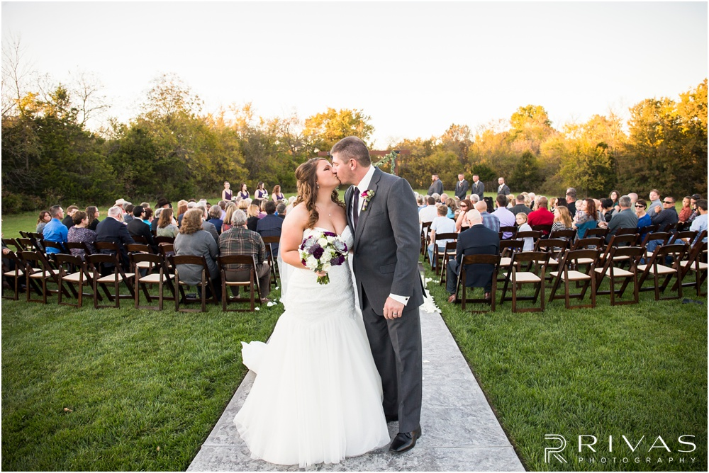 elegant fall wedding buffalo lodge | A picture of a bride and groom kissing at the end of the aisle after their sunset wedding ceremony at The Buffalo Lodge.